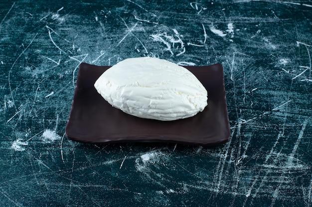 Un morceau de fromage blanc fait maison sur le plateau.