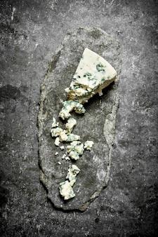 Morceau de fromage bleu français .sur la table en pierre.