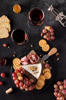 Morceau de fromage brie avec raisins, craquelins et vin rouge
