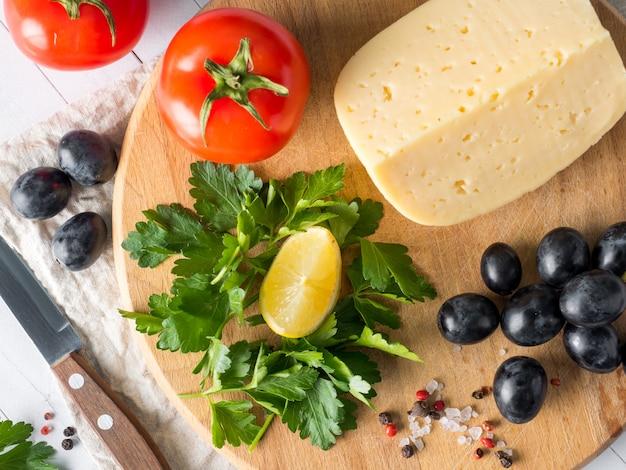 Morceau de fromage avec du persil, tomates raisins sur une planche à découper avec un couteau.