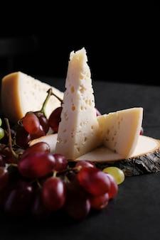 Morceau de fromage jarlsberg avec raisins sur une plaque de bois