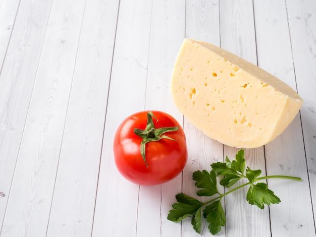 Morceau de fromage avec persil et tomate sur un fond en bois blanc.