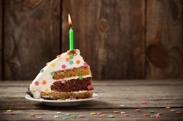 Morceau de gâteau d'anniversaire sur fond de bois
