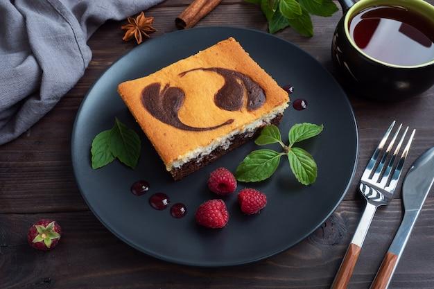 Un morceau de gâteau sur une assiette de brownies au chocolat et cheesecake caillé aux framboises