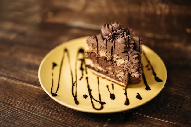 Morceau de gâteau sur l'assiette, chef-d'œuvre culinaire sur bois