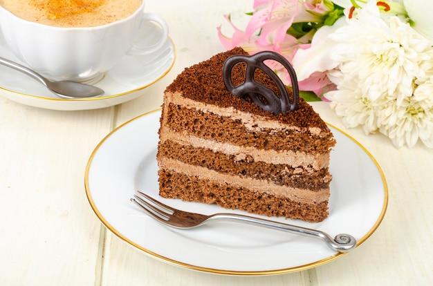 Morceau de gâteau au chocolat, cappuccino, fleurs sur table.