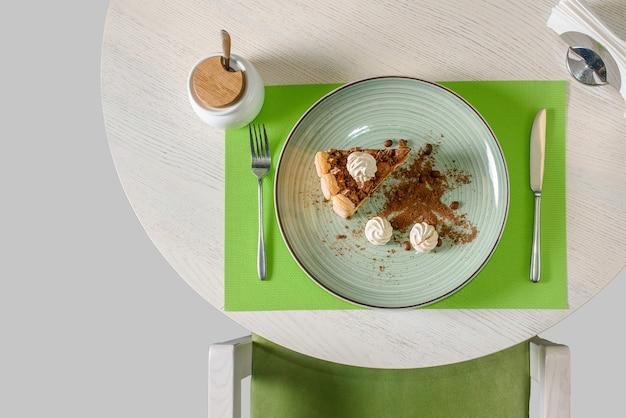Un morceau de gâteau au chocolat décoré de meringues, grains de café et miettes de biscuit, cappuccino. dessert tiramisu, vue de dessus.