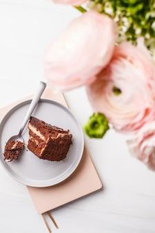 Morceau de gâteau au chocolat en plaque grise sur fond blanc.