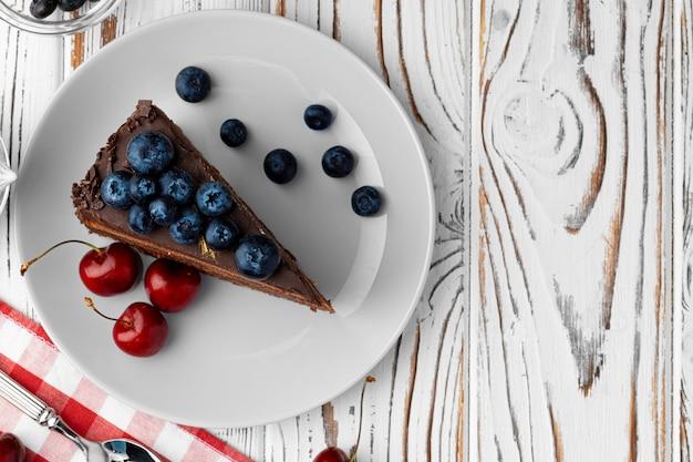 Morceau de gâteau au chocolat servi avec des baies fraîches
