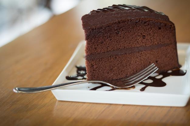 Morceau de gâteau au chocolat avec sirop de chocolat chaud (flou artistique)