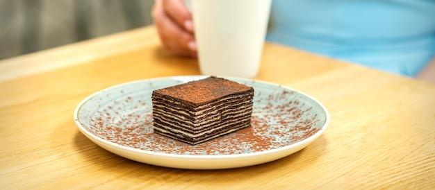 Morceau de gâteau au chocolat avec une tasse de café