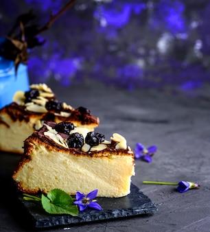 Morceau de gâteau au fromage sur une ardoise noire