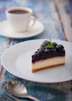 Morceau de gâteau au fromage aux bleuets sur plaque blanche sur fond de bois