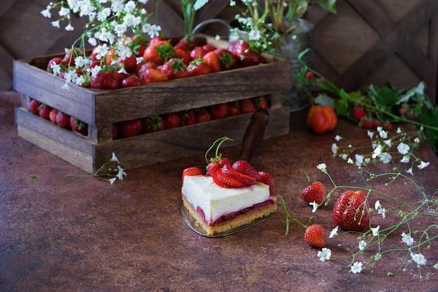 Morceau de gâteau au fromage aux fraises et une boîte en bois avec des baies de fraises fraîches et des fleurs blanches sur brun