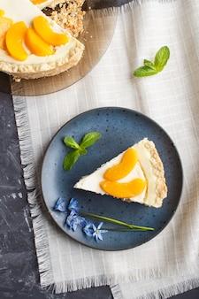 Un morceau de gâteau au fromage aux pêches sur une plaque en céramique bleue avec des fleurs bleues sur un espace de copie de fond en béton noir