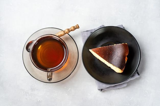 Un morceau de gâteau au fromage brûlé basque avec une tasse de thé noir