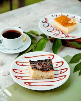 Morceau de gâteau au fromage garni de sirop de chocolat servi avec du thé