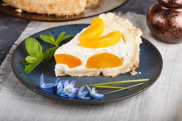 Un morceau de gâteau au fromage à la pêche sur une assiette en céramique bleue avec des fleurs bleues et une tasse de café sur fond noir