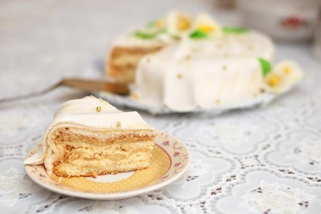 Morceau de gâteau au mastic blanc décoré de fleurs, gros plan