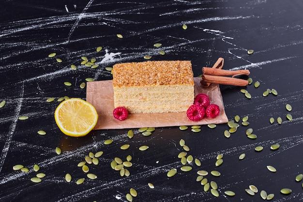 Un morceau de gâteau au miel avec des baies et de la cannelle sur une table en marbre.