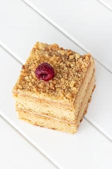 Un morceau de gâteau au miel fait maison sur une table en bois blanc. mise au point sélective.