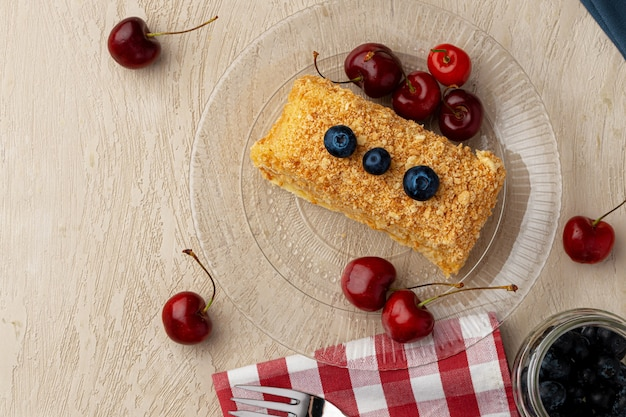 Morceau de gâteau au miel russe medovik servi avec des baies fraîches