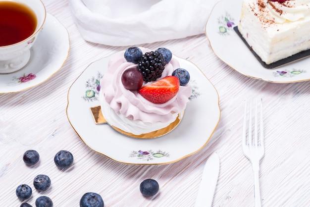 Morceau de gâteau aux baies décoré de baies fraîches sur fond blanc en bois