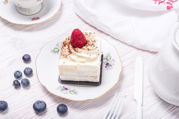Morceau de gâteau aux baies décoré de fraises fraîches sur fond blanc en bois