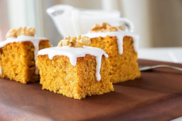 Morceau de gâteau aux carottes fait maison avec des noix et de la crème glacée.