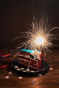 Morceau de gâteau aux couleurs du drapeau américain avec des cierges magiques sur fond sombre, célébration de la fête de l'indépendance, concept du 4 juillet, gros plan.