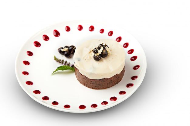 Un morceau de gâteau aux crêpes avec un chapeau de baies aspergées de chocolat blanc sur une plaque avec des muffins belges sur un tableau blanc