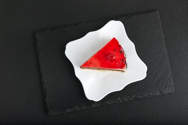 Morceau de gâteau aux fruits rouges sur plaque blanche. vue de dessus du gâteau sur fond noir.