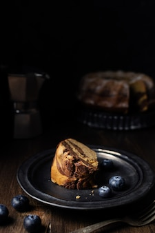 Morceau de gâteau bundt au chocolat et à la vanille servi avec des bleuets et du café