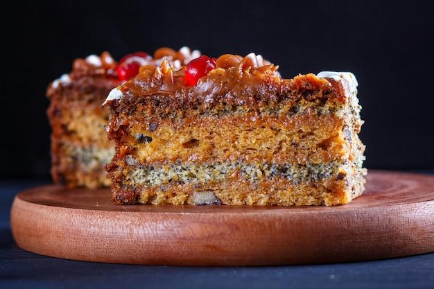 Un morceau de gâteau avec de la crème au caramel et des graines de pavot sur une planche de cuisine en bois, fond noir.