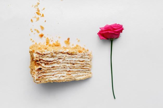 Un morceau de gâteau crémeux avec une rose sur fond blanc. vue de dessus.
