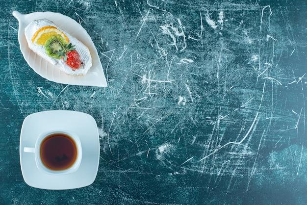 Un morceau de gâteau crémeux avec une tasse de thé chaud. photo de haute qualité