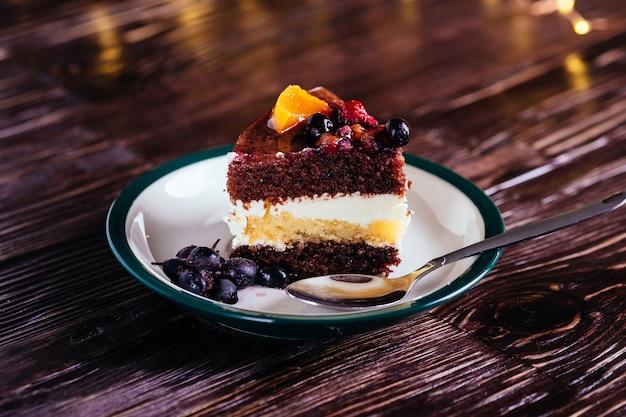 Un morceau de gâteau avec du chocolat à la crème et des fruits