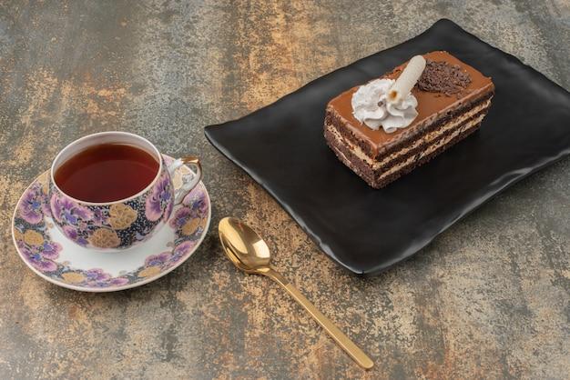Un morceau de gâteau avec du thé chaud et une cuillère sur une assiette sombre