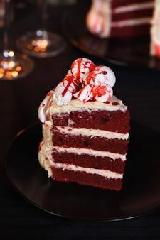 Un morceau de gâteau effrayant en velours rouge décoré d'os de meringue et trempé de sang