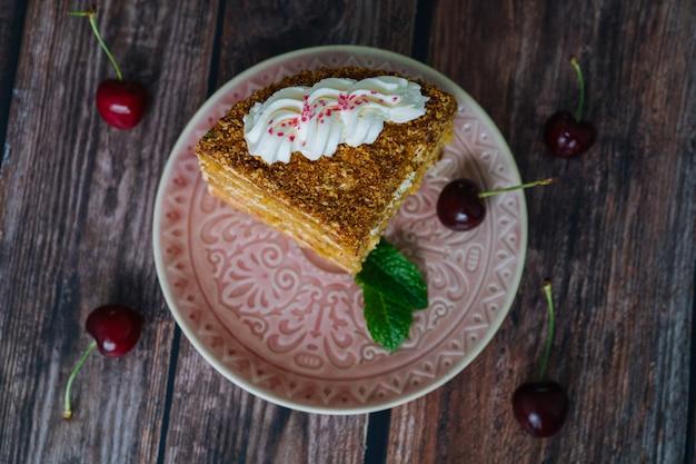 Morceau de gâteau multicouche avec de la crème sur une assiette. morceaux de gâteau au miel classique avec crème anglaise.