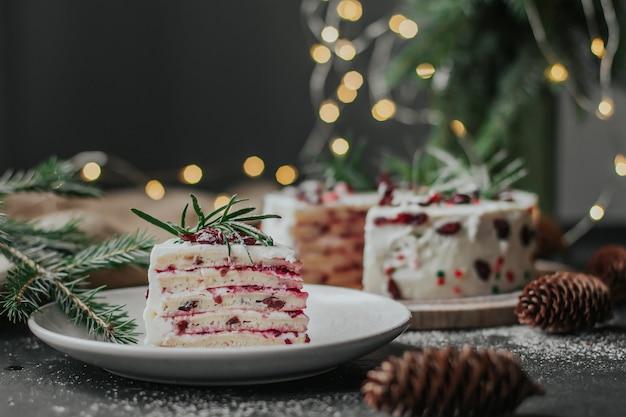 Un morceau de gâteau de noël sur une plaque blanche dans le contexte de branches de sapin et de guirlandes.