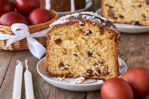 Morceau de gâteau de pâques avec des œufs de couleur brune sur une table en bois