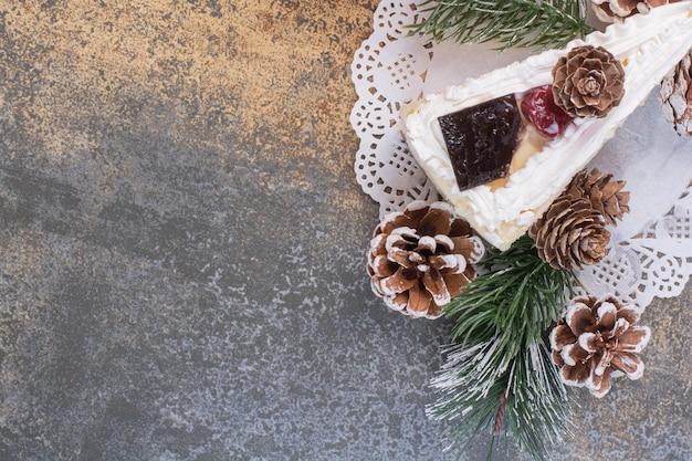 Un morceau de gâteau avec des pommes de pin sur une surface en marbre