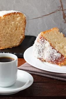 Morceau de gâteau recouvert de noix de coco et de café noir.