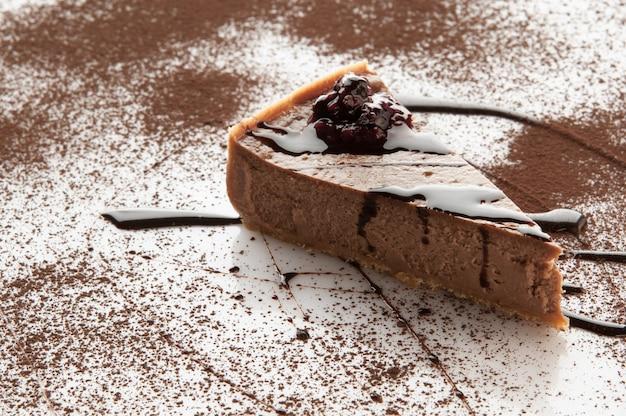 Un morceau de gâteau saupoudré de sucre en poudre sur fond blanc