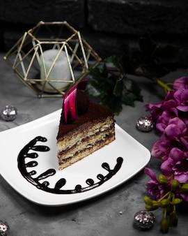 Morceau de gâteau servi avec décoration chocolat dans l'assiette