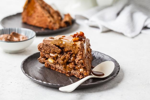 Morceau de gâteau de snickers fait maison avec crème au chocolat et caramel sur une soucoupe noire, fond blanc.