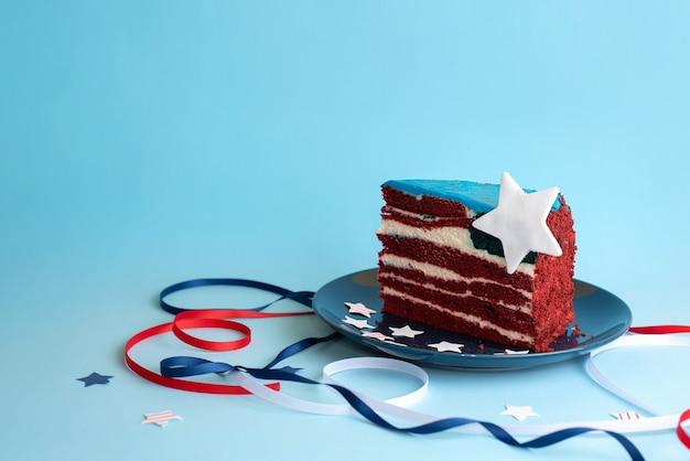Un morceau de gâteau sous la forme du drapeau des états-unis avec des rubans et des étoiles blancs, rouges et bleus sur fond bleu, célébrant le jour de l'indépendance, en gros plan.