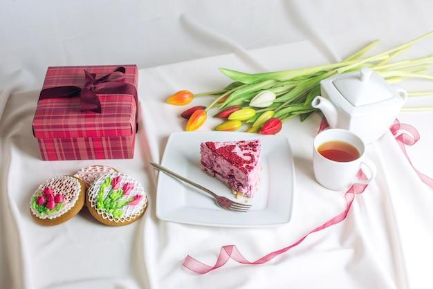 Morceau de gâteau avec une tasse de café et des tulipes