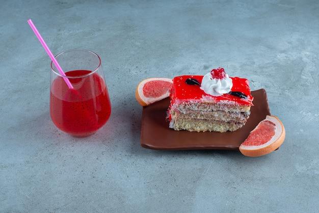 Un morceau de gâteau avec une tasse en verre de jus rouge.